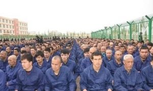Detainees in a Xinjiang, China Re-education Camp located in Lop County listen to