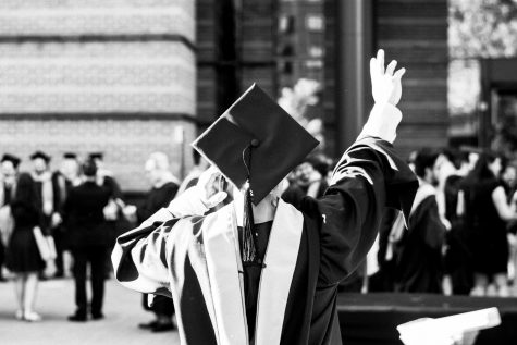 A college graduate throws a hand in the air to celebrate their most recent accomplishment.