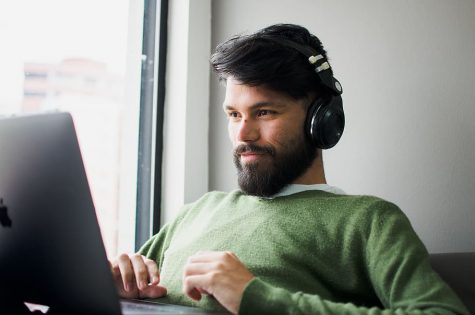 A mean wearing headphones uses his computer.