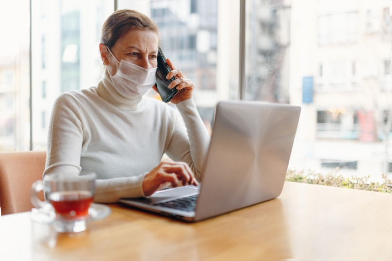 A woman works at her laptop while wearing a protective mask.