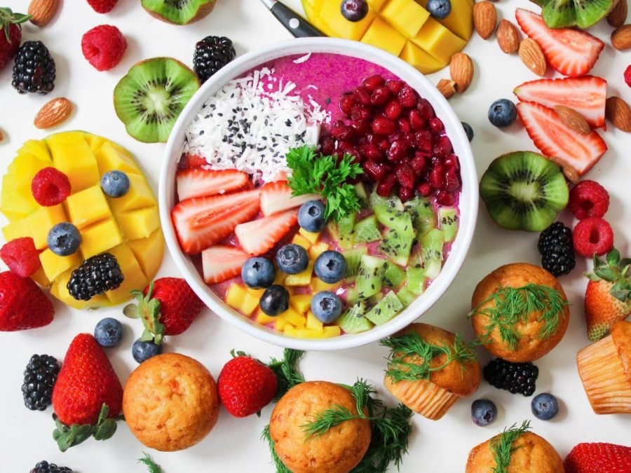 An assortment of fruit surround and fills a white ceramic bowl.