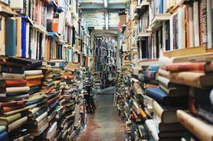 Stacks and shelves of books line the edges of a narrow corridor.