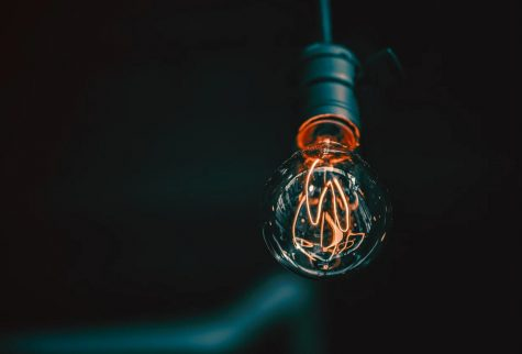 A light bulb hangs from a wire in a dimly lit environment.