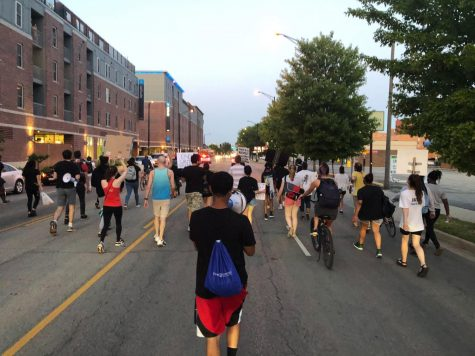 Demonstrators march down Unviersity Avenue in Champaign, IL on June 16 during a protest sparked by the reinstatement of the Urbana Police Chief Bryant Seraphin.