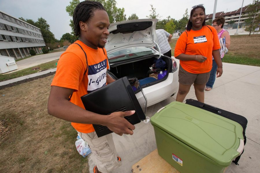 An I-Guide helps a student moving into a dorm in the Ikenberry Commons move their things from a car to a cart on Aug. 22, 2013.