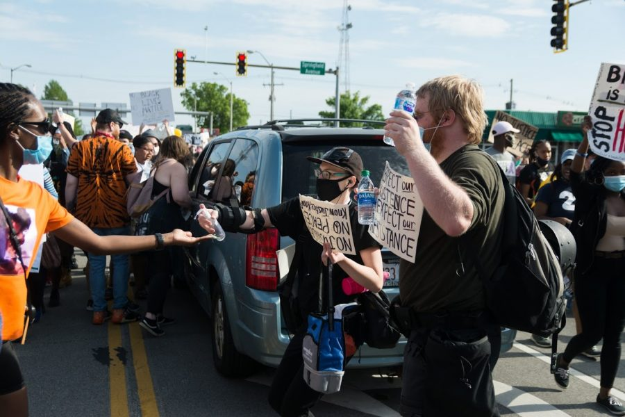 At the intersection of Springfield Avenue and Neil Street, supporters of the protest create an aid station offering free water and hand sanitizer.