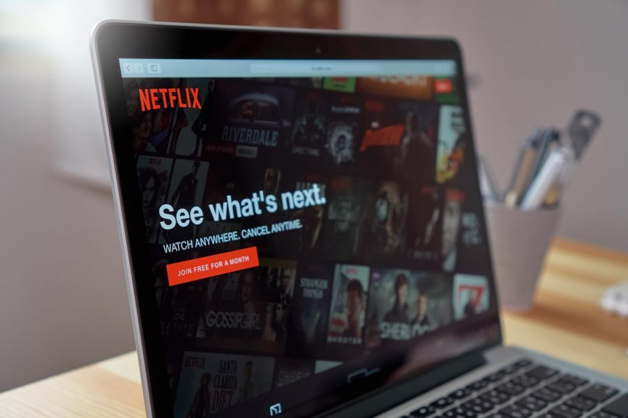 The Netflix homepage displays itself on a laptop screen
