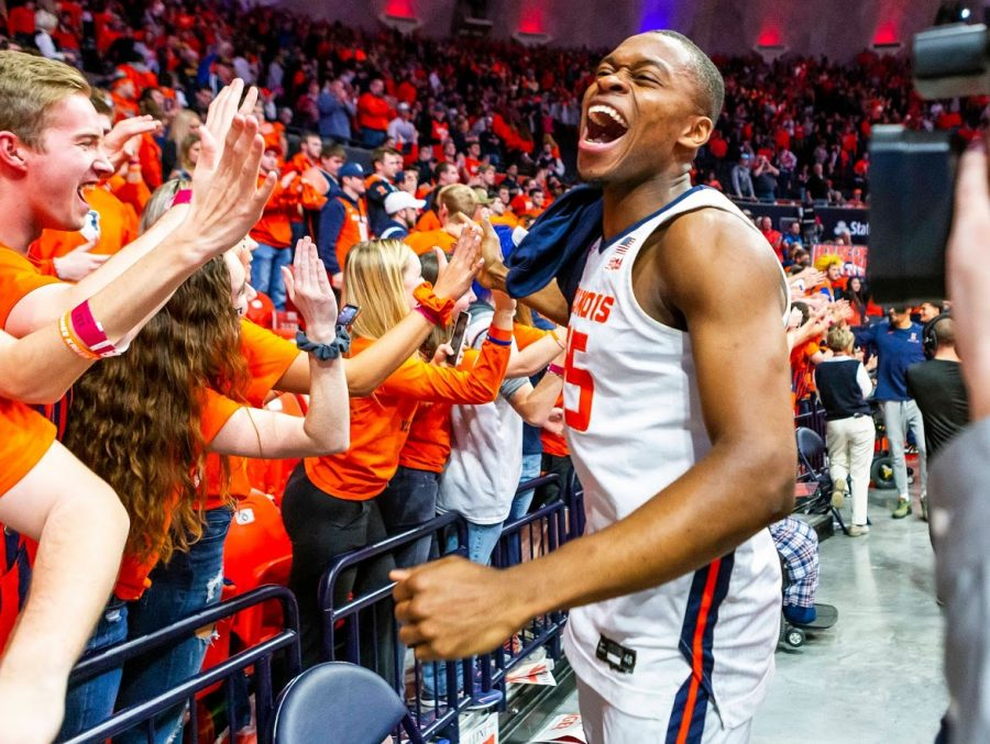 Students+in+the+fan+section+high+five+senior+Samson+Oladimeji+at+the+basketball+match+against+Iowa+on+March+8.