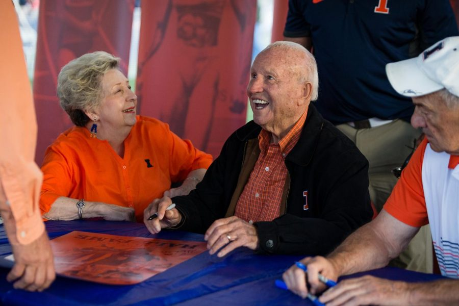 Former Illinois basketball head coach Lou Henson signs autographs for fans before the game against Penn State at Memorial Stadium on Friday, Sept. 21, 2018. The Illini lost 63-24.