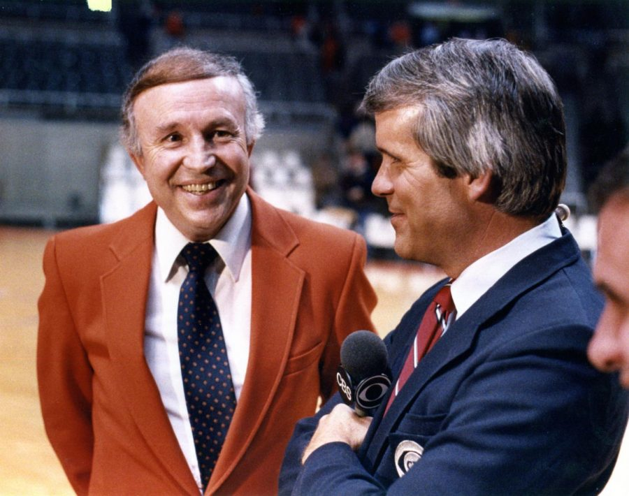 Former Illinois Basketball Coach Lou Henson smiles as he is interviewed by a CBS reporter on the court.