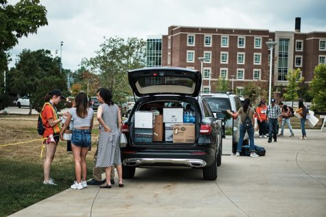 I-Guides assist multiple families near their cars as they move their children into the dorms on Aug. 22, 2019.
