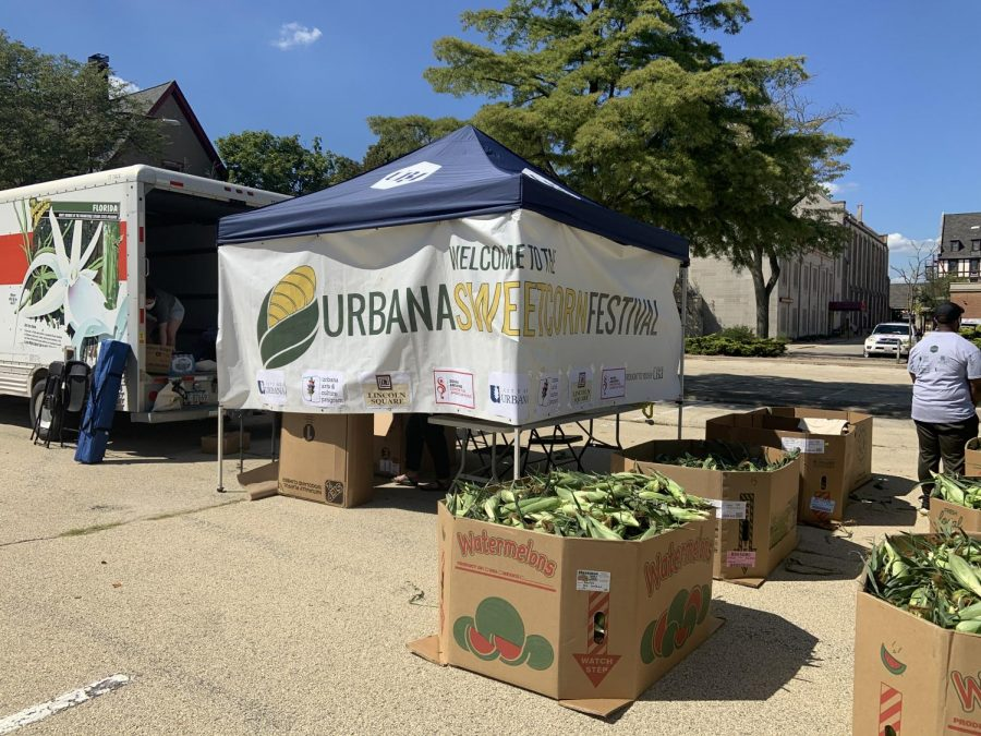 The organizers of the Urbana Sweetcorn Festival set up a stand in the parking lot of the Lincoln Square Mall. Community members can drive by and pick up bags of sweet corn as well as commemorative totes and face masks.