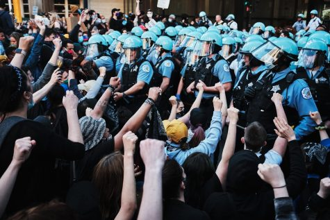 Chicago police officers form a line in front of demonstrators during a protest on May 30. Columnist Maii argues the CPD is responsible for much of the violence occurring on Aug. 15.