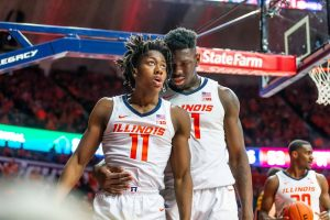 Freshman Kofi Cockburn embraces Sophomore Ayo Dosunmu during the match against Iowa at State Farm Center in Champaign, Illinois on Sunday, March 8..