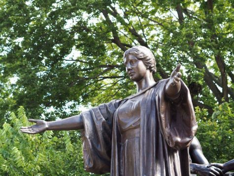 The Alma Mater statue stands proudly with her arms spread wide on a summer day.