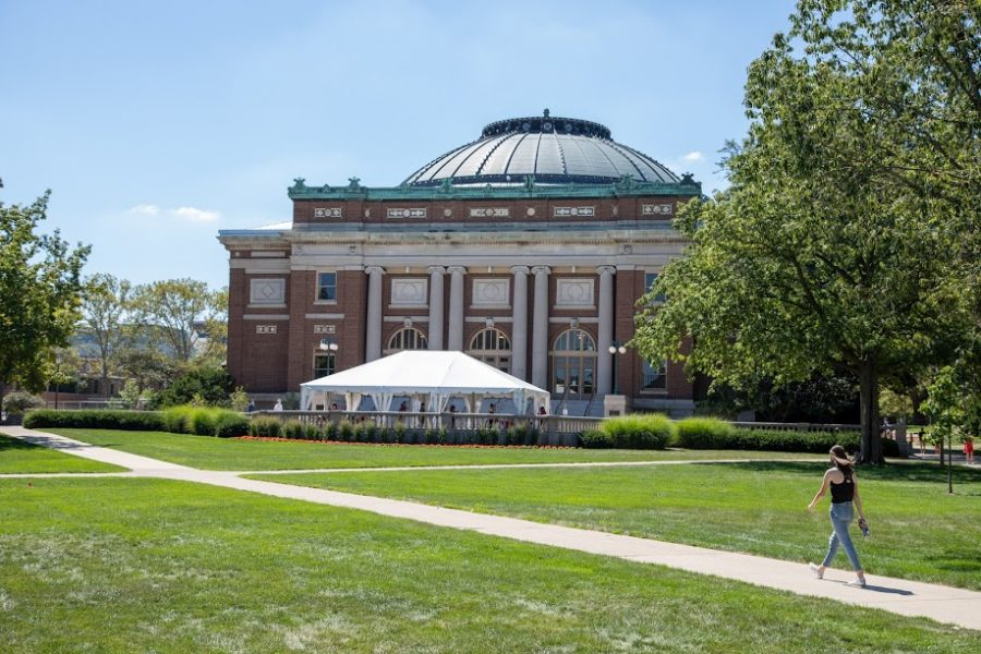 A student walks past the Foellinger Auditorium COVID-19 testing tent on the Main Quad on Aug. 21. According to a Massmail sent on Thursday, students will be granted building access from the time they receive a negative test result until 11:59 p.m. on the fourth day after they take the test.