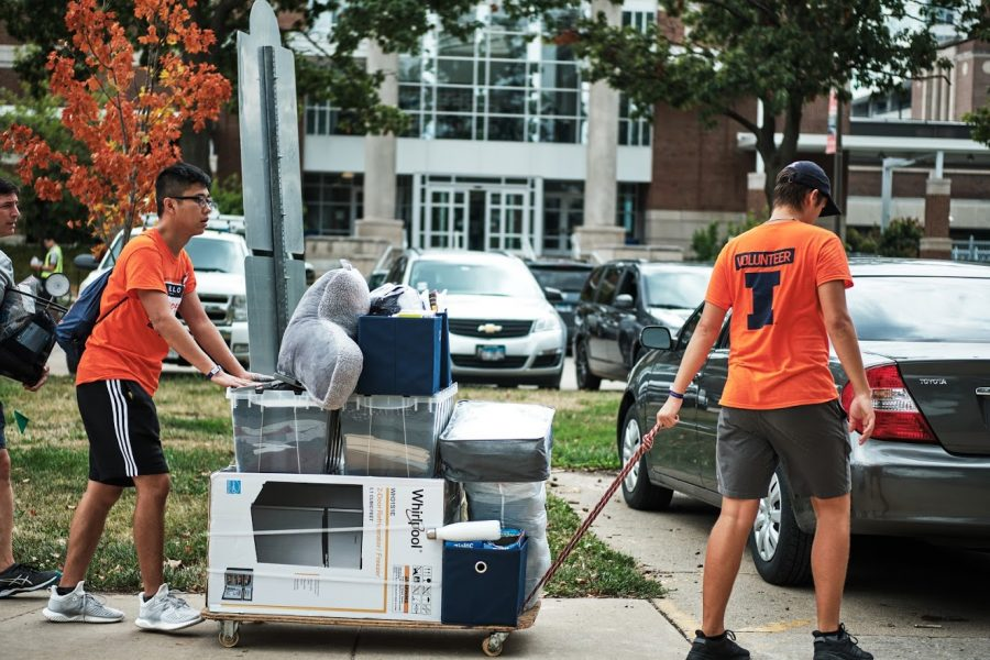 Two I-Guides push a cart loaded with a student's items during move-in on Aug. 22, 2019.