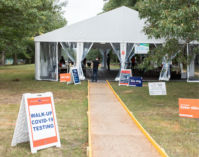 Students stand in line to be tested at the Stanley Illini Grove COVID-19 testing tent on Wednesday. 182,060 saliva tests have been administered since the beginning of on campus testing.