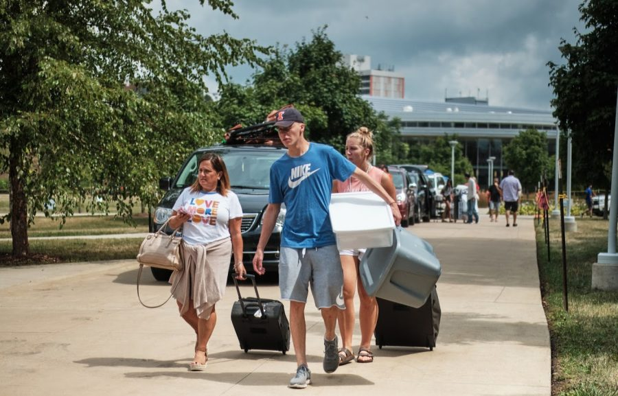 A family helps carry their student's belongings to their dorm during move-in on Aug. 22, 2019.