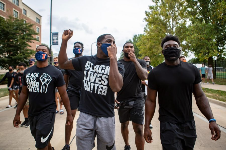 Illini football players Delano Ware, Moses Okpala, Jartavius Martin, Owen Carney, and Khalan Tolson march down First Street to protest police brutality in the black community on Monday afternoon.