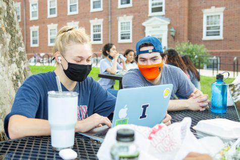 A pair of masked students look at a laptop while sitting at a table outside of Lundgren Hall on Sunday. After a spike in positive cases during week two, the positives lessened in week three.