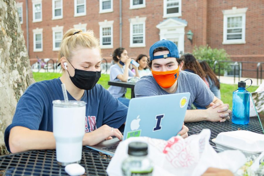 A pair of masked students look at a laptop while sitting at a table outside of Lundgren Hall on Sunday. Twenty-eight Illinois counties are reported to be at a warning level for the novel coronavirus.