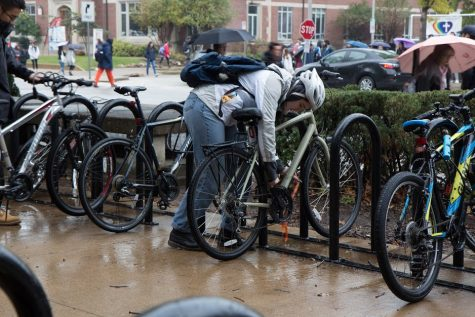 A student unlocks their bike outside the English Building on Oct. 26, 2018. The University will soon be implementing a new bicycle registration database called 529 Garage.