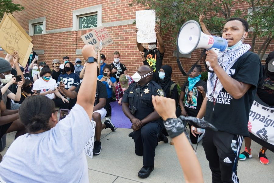 Champaign Police Chief Anthony Cobb kneels with protestors as organizer Drake Materre speaks outside of the Champaign Police Department during a protest following the death of George Floyd on June 1. New listening sessions will allow the community to address public safety needs.