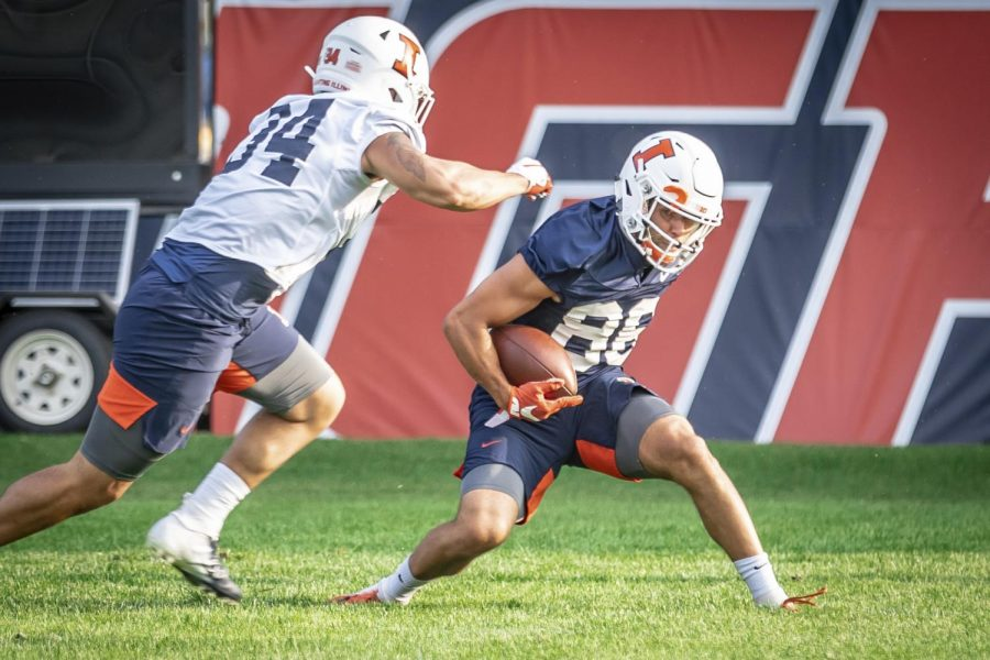 Junior Donny Navarro slips around a defender during football practice on Sept. 17. The Illini are scheduled to have their first home game of an abbreviated 2020 season on Halloween against Purdue.
