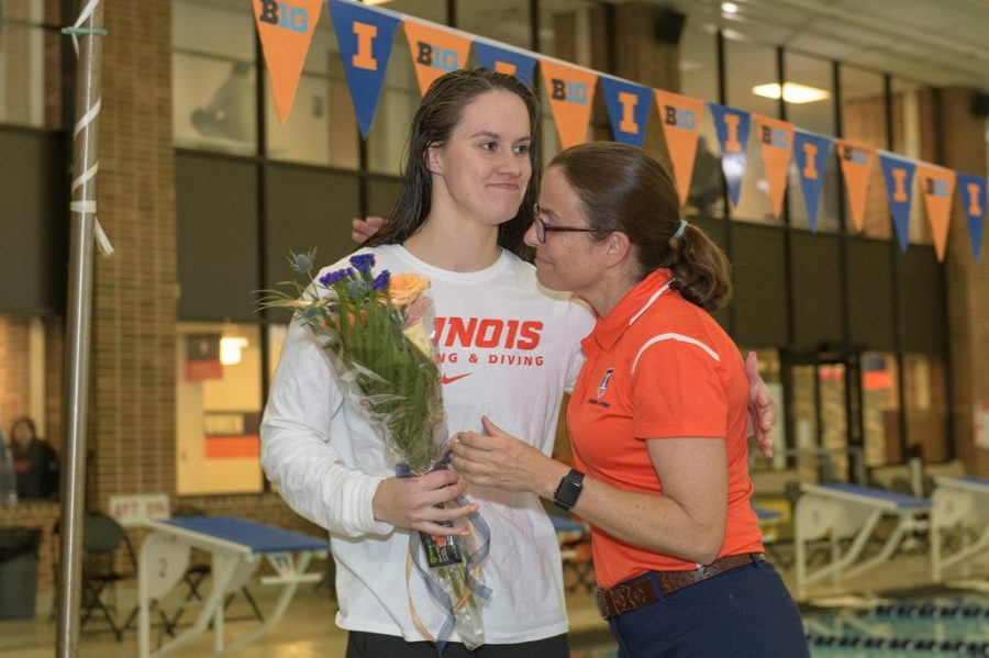Women's swimming head coach Sue Novitsky hugs senior swimmer Gabriele Serniute during Senior Day on Jan. 26, 2019. Novitsky felt shocked upon hearing about Iowa's program cuts.