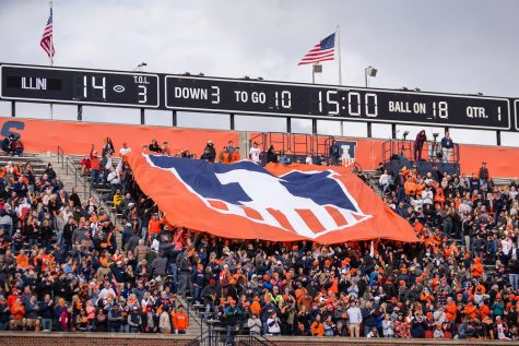The Block I student section hoists a banner with the Illinois shield logo during the game against Minnesota at Memorial Stadium on Nov. 3, 2018. Though the north stands will be empty this season, fans are still excited about the return of Big Ten football.