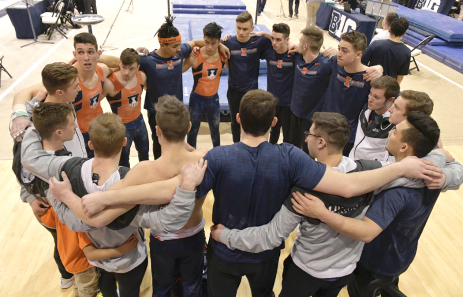 Members of the Illinois men's gymnastics team lock arms in a circle at a gymnastics meet during the 2019 season..