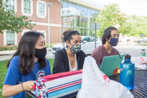 Three students sit at a table outside of Lundgren Hall on Sunday. Champaign County reported 136 new cases of COVID-19 on Sunday, bringing the total number of active cases in the county to 323.