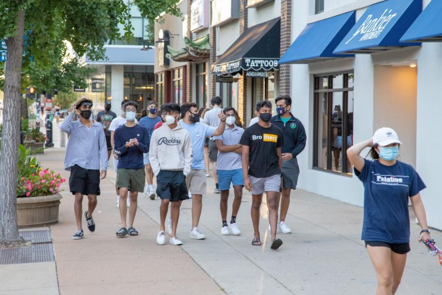 A+group+of+students+wearing+masks+walks+down+Green+Street+on+Aug.+21.+Several+entities+are+currently+under+investigation+for+coronavirus+violations.+Jones+believes+that+the+spike+in+COVID-19+cases+on+campus+are+not+due+to+community+spread.+