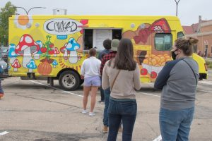 People wait in line to order at the Cracked the Egg Came First food truck at Lincoln Square Farmers Market in Urbana on Saturday.