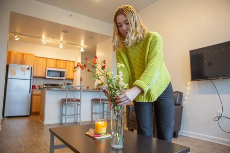 Sophomore Natalie Bizon adjusts the flowers in her apartment on Friday. Settling into your new housing is an important part of a new school year.