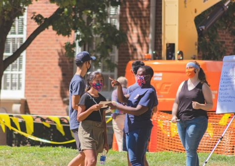 An Illinois employee hands a student a leaflet on the Main Quad on Aug. 21.