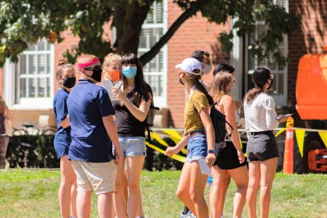 A group of students stands on the Main Quad while wearing masks on Aug. 21.