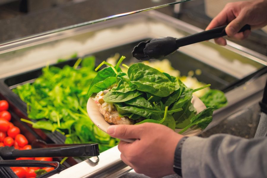 A student puts greens on their plate at a salad bar located in the SDRP on April 27, 2018. Researchers at the University have recently investigated claims surrounding vegetables.