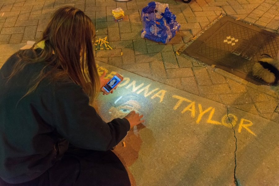 A+protester+draws+Breonna+Taylor%27s+face+in+chalk+on+the+sidewalk+outside+the+Champaign+Police+Department.+Demonstrators+gathered+Wednesday+in+response+to+the+grand+jury+decision+regarding+the+killing+of+Breonna+Taylor.