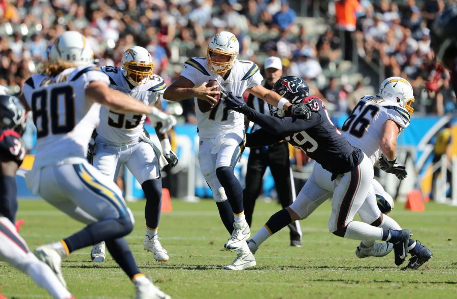 Los Angeles Chargers quarterback Philip Rivers tries to evade the sack of Houston Texans outside linebacker Whitney Mercilus  and ends up fumbling on the play in the second half at Dignity Health Sports Park on Sept. 22, 2019 in Carson, CA.