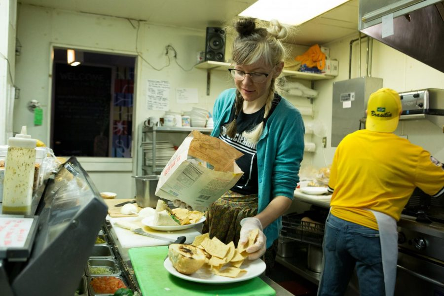 Paula Chmiel prepares an order with chips at Red Herring Vegetarian Restaurant on Nov. 28, 2018. The establishment is one of several vegetarian options available in Champaign.