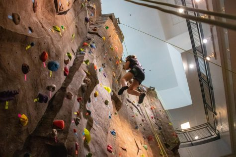 Sophomore Mary Pelzer scales the rock climbing wall in the ARC on Saturday afternoon.