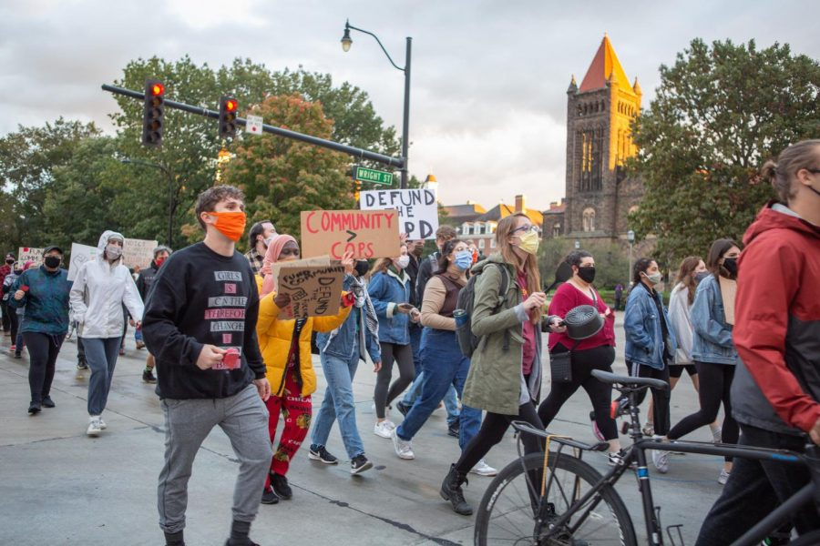 Demonstrators+march+through+the+intersection+of+Green+Street+and+Wright+Street+during+the+UIPD+protest+on+Thursday.+Protesters+marched+from+the+Illinois+Police+Department+Headquarters+to+the+University+of+Illinois+Police+Training+Institute.