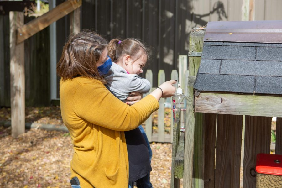 A girl and her mother use a hand sanitizing station at the Curtis Orchard & Pumpkin Patch on Oct. 14.