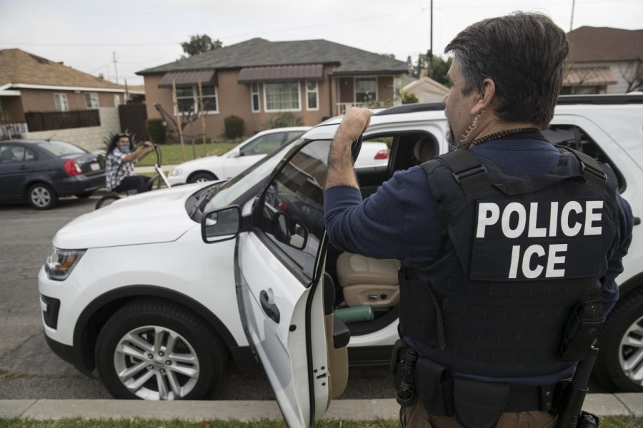 """ICE agent Jorge Field stands outside the home of a 47-year-old Mexican national in Montebello, California. The University opposed a rule to eliminate """"Duration of Status"""" admission."""