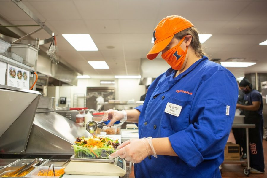 "A FSHN 340: Food Production and Service student prepares a salad while working at the Bevier Cafe located in Bevier Hall on Friday. The Bevier Cafe has recently established its ""Everybody Eats"" initiative to fight food insecurity."