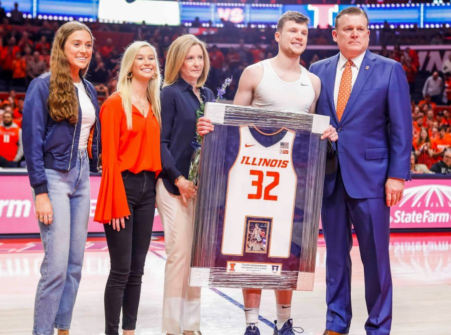 Former Illinois basketball player Tyler Underwood stands with his family, including basketball Head Coach Brett Underwood, during senior night on March 8 at State Farm Center.
