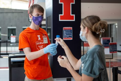 A University coronavirus testing site worker hands junior Jessica Wynveen a test tube at the State Farm Center testing site on Oct. 9. While Illinois is experiencing a rise in positivity rate, Champaign County has seen a steady rate, with UI depressing the region's positivity.