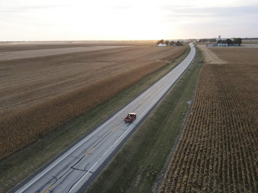 A truck drives between two cornfields on E. Country Rd 1000 N.